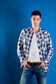 homem jovem bonito com camisa xadrez calcas jeans femininas em fundo azul