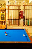 Billiard club with blue pool table cue in a row and winner trophy