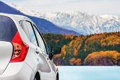 Road Trip Concept, Car Driving Travel In Autumn Season, Lake, Beautiful Foliage And Mountains Covere poster