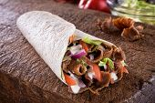 A Delicious Doner Donair Kebab Wrap With Spicy Meat, Lettuce, Tomato, Red Onion And Sauce. poster