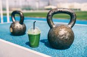 Health and fitness green smoothie detox drink at gym with kettlebells weights at outdoor training fi poster