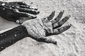 Close Up Of Woman Hands Painted Black On Sand. Conceptual Image poster