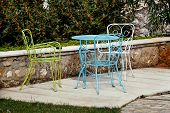Chairs And A Table In Garden. Colorful Steel Chairs And A Table Standing In A Beautiful Garden At Su poster