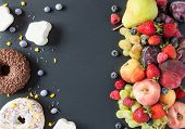 A Lot Of Natural And Healthy Vitamin Fruits, Berries Vs Sweet And Junk Food On A Black Background. V poster