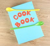 Cookbook and kitchenware on wooden background