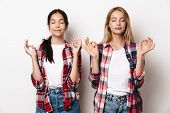 Image of a pretty pleased young girls friends sisters posing isolated over white wall background med poster