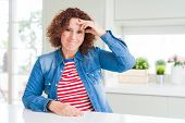 Middle age senior woman with curly hair wearing denim jacket at home worried and stressed about a pr poster