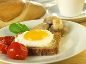 foto of crimini mushroom  - Sunny side up egg on a slice of bread with tomatoes and mushrooms on a plate with a French loaf and tea cup in the background - JPG