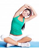 beautiful young brunette woman stretching the muscles of her arms and back, isolated against white b