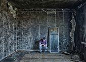 sad man, sitting  in burnt  room