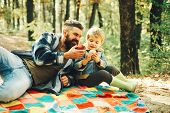 Dad And Son Inautumn Park. Dad And Son In The Autumn Park Play Laughing. Happy Joyful Father With A  poster