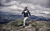 Hipster Feels Free While Hiking, Sky Background. Hipster Or Brutal Macho Conquers Mountain. Man With poster