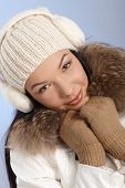 Attractive young female at winter in white cap and coat and earmuffs.