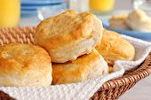 Basket of freshly baked biscuits with orange juice and tableware in background.  Closeup with shallo