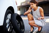 stock photo of breakdown  - Woman calling for assistance with flat tire on car in the city - JPG