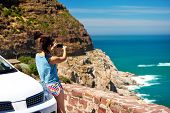 Tourist woman taking a photograph of scenic ocean mountain road chapmans peak in cape town south afr