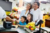 stock photo of local shop  - Family looking out for home finances at the supermarket - JPG