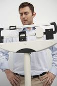Middle aged man looking at scale of weighing machine