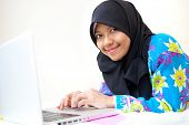 Beautiful young Muslim woman student using laptop