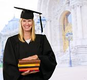 Happy Graduate Woman Holding Books in front of a university building