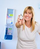 Woman Holding Stopwatch next to a phone box