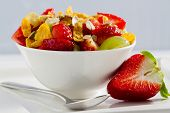 Diet, muesli with strawberry and fruit salad in the white bowl - healthy breakfast, weight loss conc