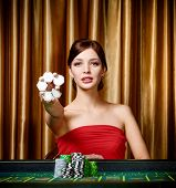 Female gambler keeps chips in hand sitting at the casino table