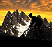 silhouette of the cyclist riding a road bike in the Italy Alps