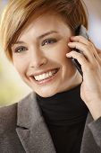 Closeup portrait of attractive young woman talking on mobile phone, smiling.