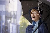 stock photo of rainy season  - Happy young woman standing under umbrella in rain - JPG