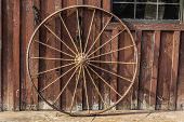 stock photo of wagon wheel  - An old rusty wagon wheel leaning on a barn wall - JPG
