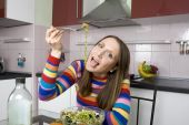 Woman Eating Salad On The Kitchen