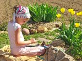 image of young girls  - young painter paints near yellow tulips at the gerden - JPG