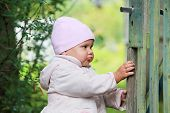Baby Girl In Pink Hat Plays With Old Green Wooden Wicket