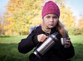 Little Beautiful Blond Girl Pours Tea From A Thermos In Autumnal Park