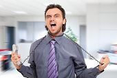 foto of strangle  - Stressed businessman using the phone cord to strangle himself - JPG