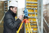 One surveyor worker working with theodolite transit equipment at road construction site outdoors