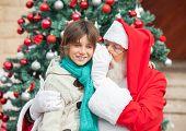 Santa Claus whispering in boy's ear against Christmas tree