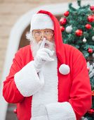 Portrait of Santa Claus gesturing finger on lips outside house