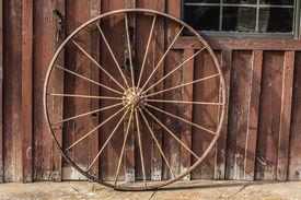 foto of barn house  - An old rusty wagon wheel leaning on a barn wall - JPG