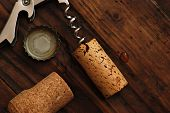 Corkscrew with corks and bottle cap on rustic wood background.  Low key still life with directional natural lighting for effect.