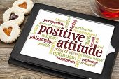 positive attitude word cloud on a digital tablet with a cup of tea and heart cookies