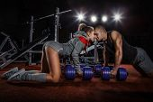 Lovely couple pushing up  with dumbbells on floor