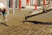 picture of concrete pouring  - Workers pouring a concrete pad outside a new commercial building - JPG