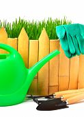 Rake, Shovel, Rubber Gloves, Watering Can Against The Wooden Fence