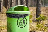 Green trash basket in forest.