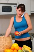 foto of long distance relationship  - woman talking on phone while unpacking groceries - JPG