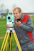 One surveyor worker working with theodolite transit equipment at spring field construction site outd