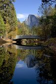 stock photo of granite dome  - Fall view of Merced River reflection of Half Dome behind Sentinel Bridge Yosemite Valley - JPG