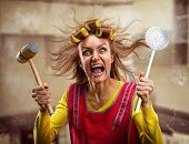 stock photo of crazy hat  - Crazy housewife with kitchen tools - JPG